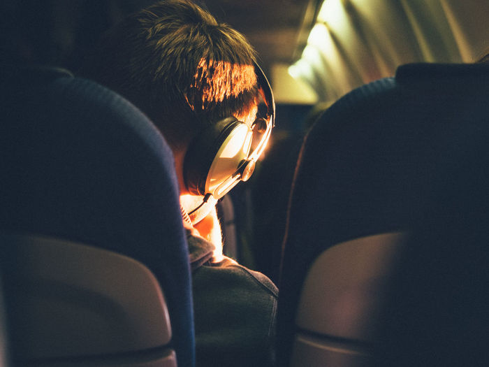Rear View Of Man Sitting In Airplane While Listening Music