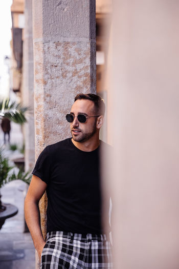 Man wearing sunglasses while standing against columns