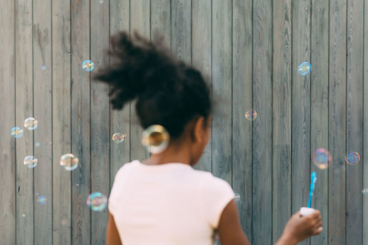 Rear view of girl blowing bubbles by wooden fence