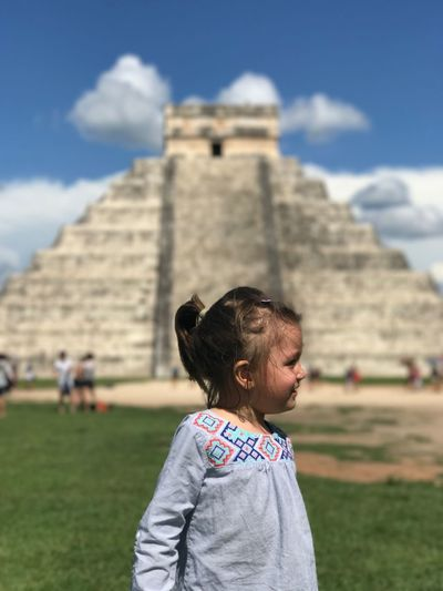 Girl standing against historic building