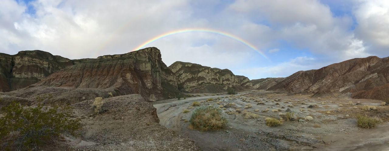 Panoramic view of rainbow over mountains against sky