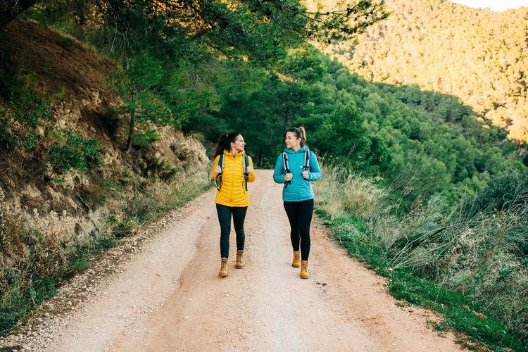 Women walking on footpath amidst plants in forest