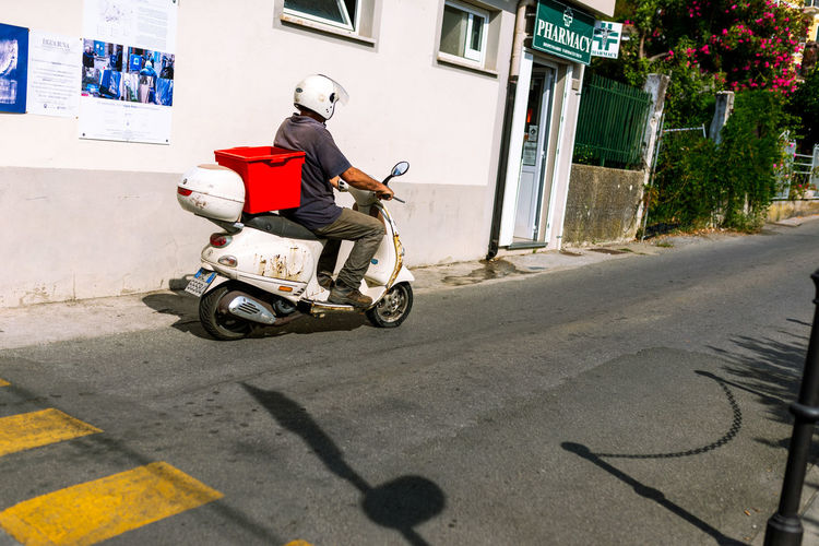 Rear view of man riding motor scooter on road