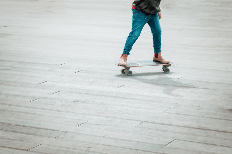 Low section of young man skateboarding on street