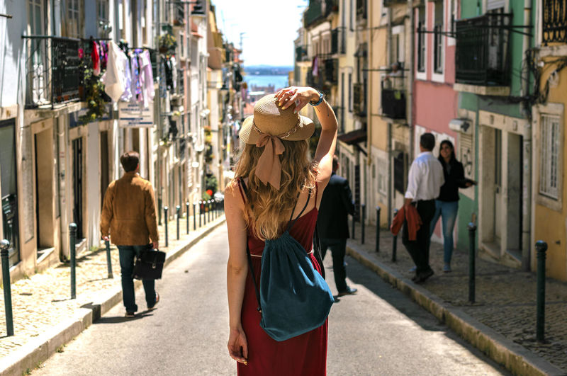 Girl wandering through city streets of Lisbon in Portugal Alfama Blonde City Hat Holiday Portugal Rear View Red Dress Trip Vacations Woman Blue Bag Culture Destination Europe Girl Lifestyles Lisbon People Popular Street Summer Tour Tourism Travel Destinations Stories From The City