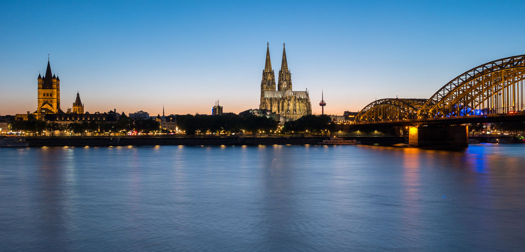 view to of old town of cologne city with cologne Cathedral at sunset Cathedral Catholic Cityscape Cologne Old Town Panorama Panoramic View Rhine Travel Arial View Blue Cityscapes Cologne Cathedral Germany Hohenzollernbrücke Illuminated Illuminated Buildings Long Exposure North Rhine Westfalia River Shore Sky Summer Sunset Travel Destinations