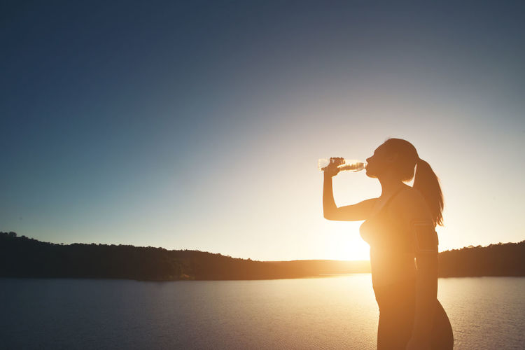 Silhouette woman drinking water while standing at lakeshore during sunset