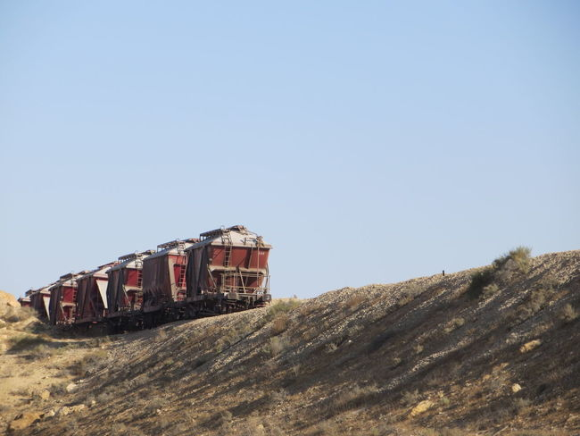 Blue Blue Sky Busy Desert Deserts Around The World Ground On The Move On The Road On Track Outdoors Pastel Colors Red Train Repetition Train Train - Vehicle Train Tracks Transportation Vehicle