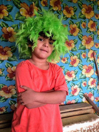 Portrait of boy wearing green wig while standing against patterned wall