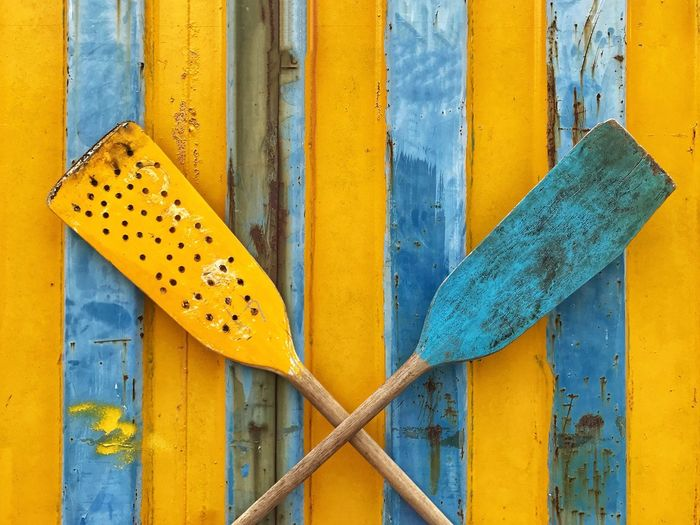 Blue and yellow rowing paddles on blue and yellow wall Travel Destinations Juxtaposition Dragonboating Rowing Paddles Hong Kong Yellow No People Day Metal Close-up Outdoors Blue Wood - Material Fence Built Structure Wall - Building Feature Backgrounds The Photojournalist - 2018 EyeEm Awards Springtime Decadence The Creative - 2019 EyeEm Awards The Mobile Photographer - 2019 EyeEm Awards