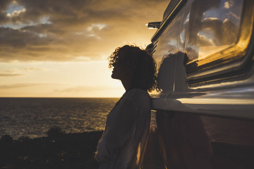 beautiful woman with blonde and curly hair traveling in vintage car Beauty In Nature Cloud - Sky Day Horizon Over Water Nature One Person Outdoors People Real People Rear View Relaxed Moments Scenics Sea Sky Standing Suggestive Place Sunset Tranquility Water Young Adult