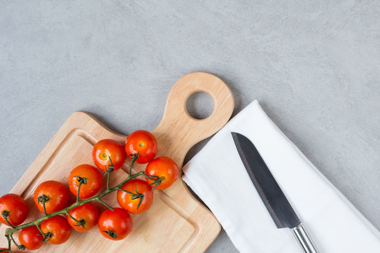 Cherry tomatoes with knife on cutting board over concreat table background , flat lay image with copy space for your text Food And Drink Food Fruit Tomato Healthy Eating Vegetable Freshness Wellbeing Indoors  Directly Above Cutting Board Wood - Material Still Life Table High Angle View No People Close-up Kitchen Knife Knife Group Of Objects Table Knife Crockery Small Group Of Objects