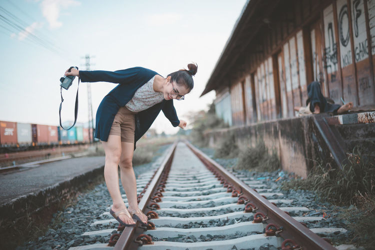Smiling young woman with camera standing on railroad track