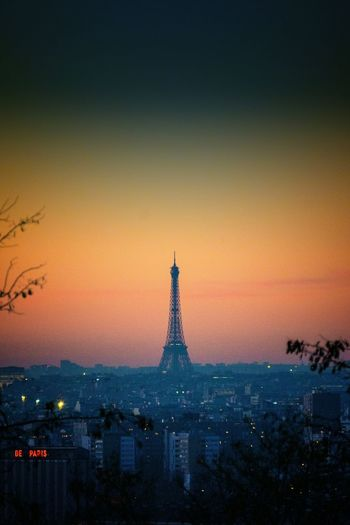 Distant View Of Silhouette Eiffel Tower In City At Sunset