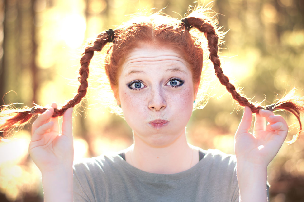 Portrait Of Woman With Puffed Cheeks Holding Pigtail Braids