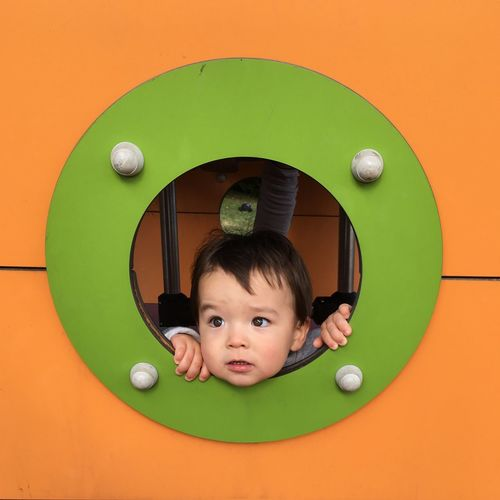 Cute baby boy looking through window of jungle gym in playground