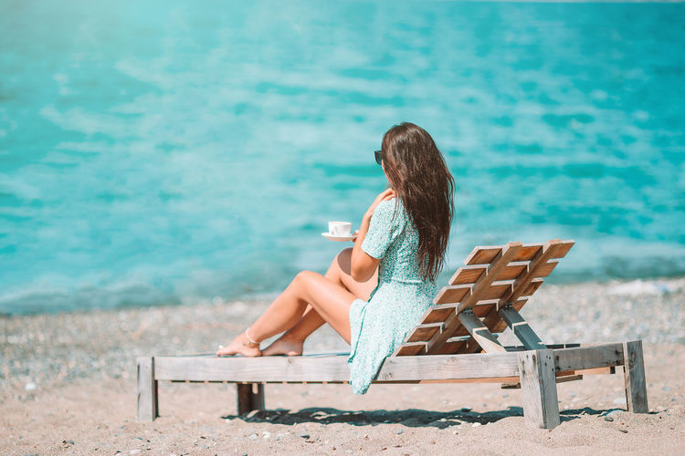 Woman holding coffee cup sitting on chair at beach