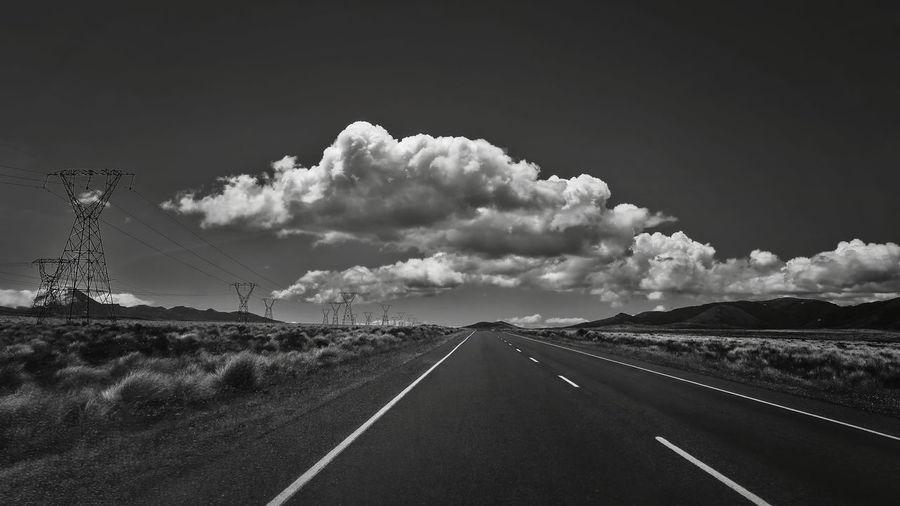 Road passing through land against sky