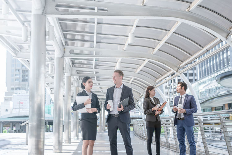 Business people discussing while standing on elevated walkway