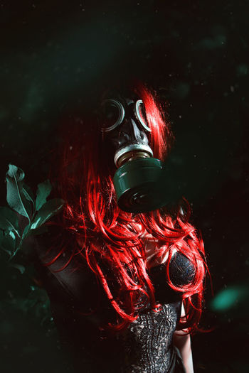 Woman with red hair wearing a soviet union gas mask