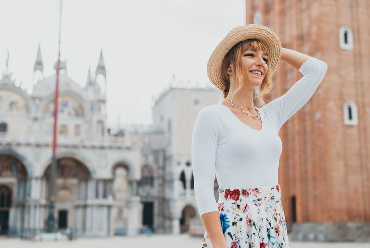 Woman wearing hat standing against building in city