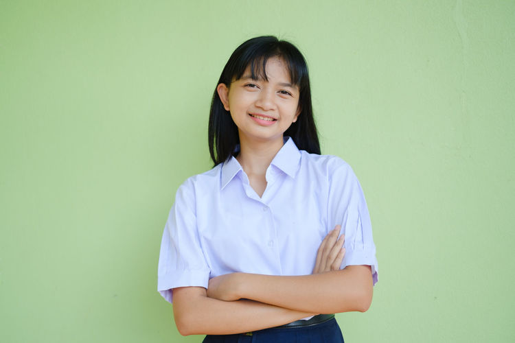 Portrait of a smiling young woman against wall