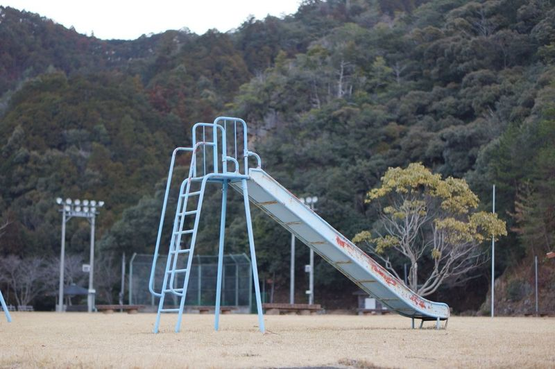 Abandoned slide on playground against trees