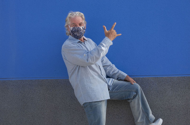 Portrait of man gesturing against blue wall