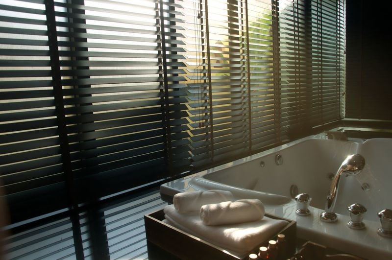 Window blinds and bathtub in restroom
