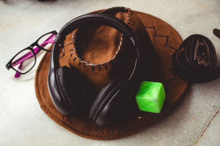 High angle view of headphones and hat by eyeglasses on table