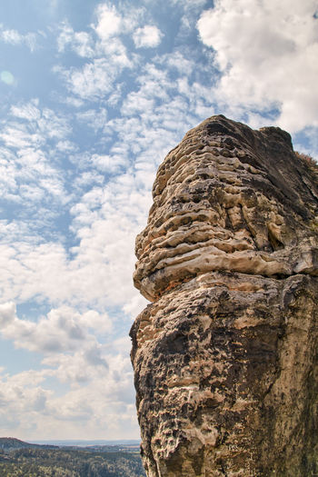 Low angle view of rock formation on sea against sky