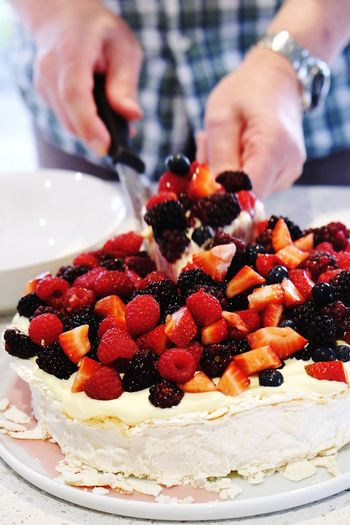 Midsection of man cutting pavlova on table