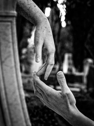 Close-up of hand touching statue