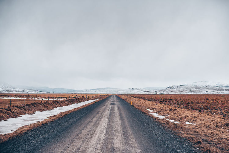 Road amidst landscape by snowcapped mountain against sky
