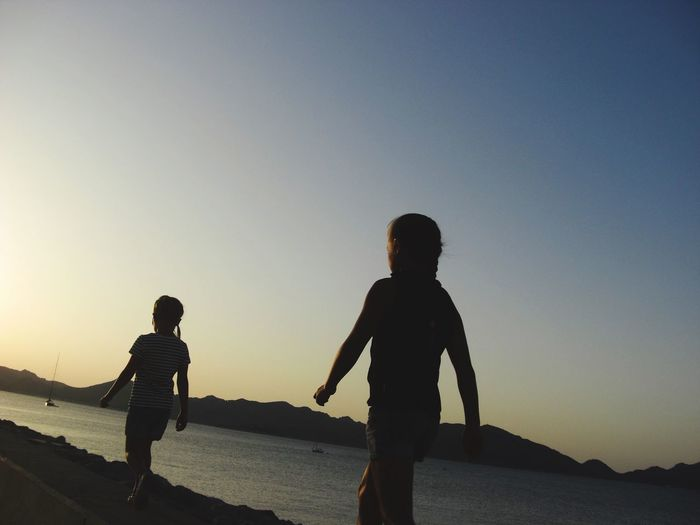 Low angle view of children at beach during sunset