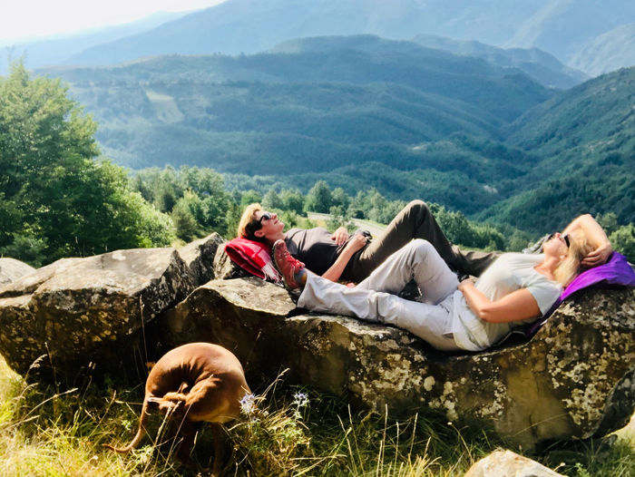 People relaxing on land against mountains