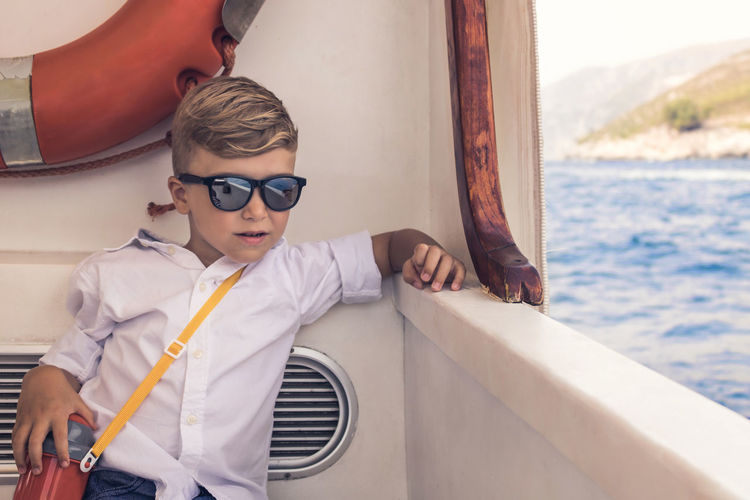 Cute boy wearing sunglasses while sailing in ferry