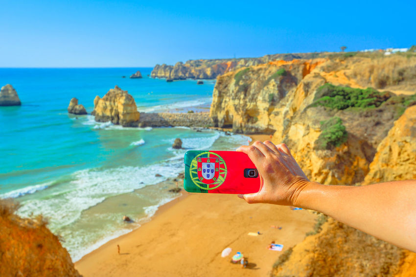 Tourism and travel concept in Algarve. Mobile phone with Portugal flag cover taking photos of Praia do Pinhao in Lagos on Algarve coast, Portugal, Europe. In the distance the famous Dona Ana Beach Lagos Portugal Algarve Portugal Algarve Coastline Algarve Beach Algarve Cliffs And Beach Beach Sea Town Seascape Boat Portrait Pier Aerial View Cliff Jetty Boats Woman Females Girl Selfie Model Camilo Beach Praia Dona Ana Praia Water Human Hand Hand Human Body Part Land Sky One Person Horizon Scenics - Nature Nature Holding Horizon Over Water Day Technology Photography Themes Rock Rock - Object Outdoors