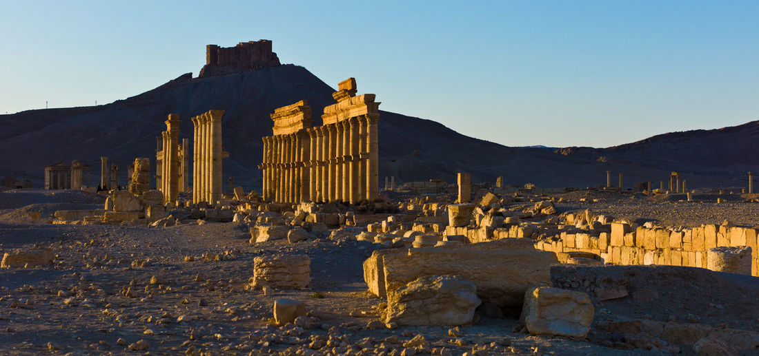 Old City of Palmyra with Muslim Palce in the background Architecture History Sky Built Structure The Past Travel Destinations No People Ruined Archaeology Mountain Clear Sky Ancient Old Ruin Travel Tourism Ancient Civilization Nature Building Exterior Old Building Solid Day Outdoors Cardo Maximus