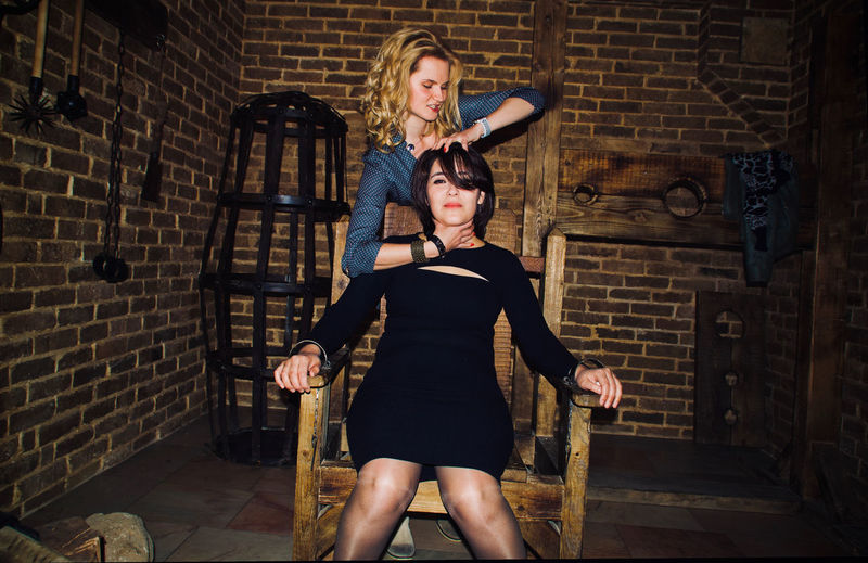 Woman torturing trapped female on chair