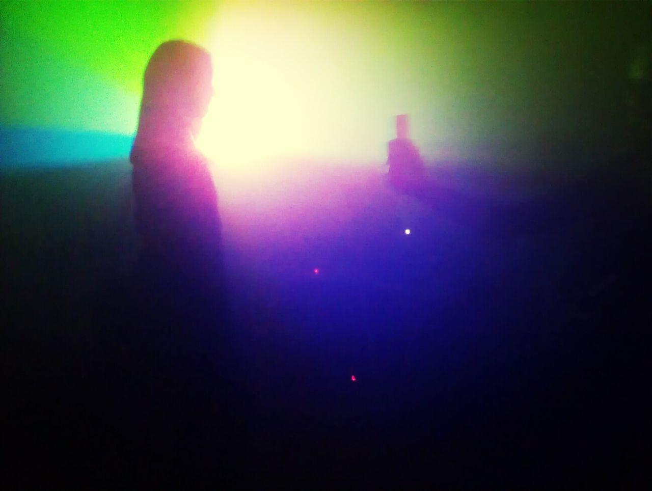 Defocused image of young women dancing at nightclub