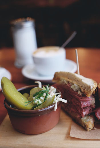Close-up of pastrami sandwich and pickles on tray
