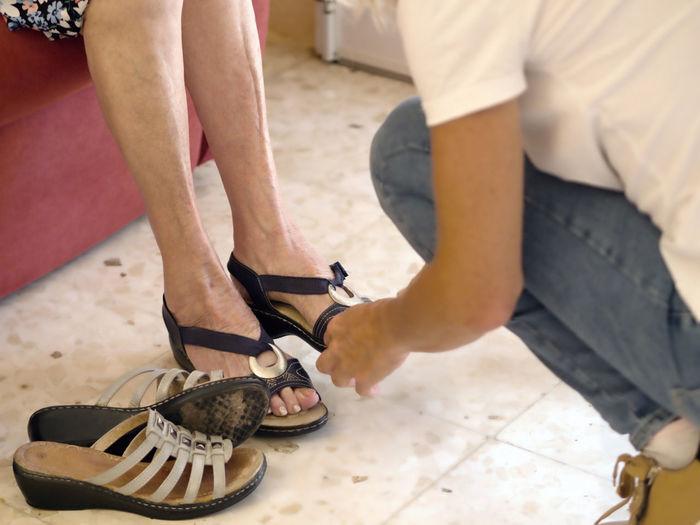 Shoe salesman assisting woman in shop