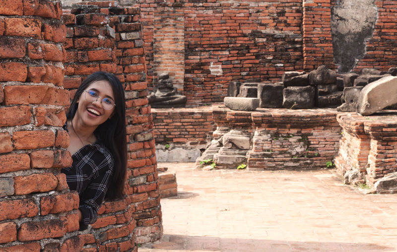 Portrait of smiling young woman against brick wall