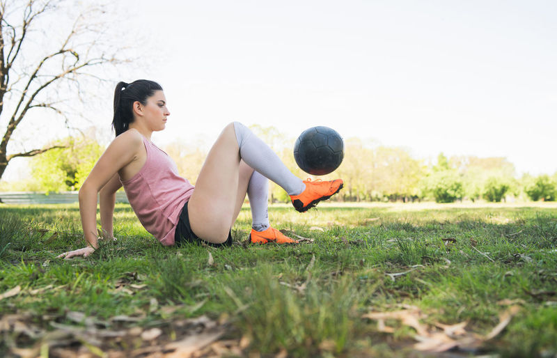 Side view of woman playing ball on field