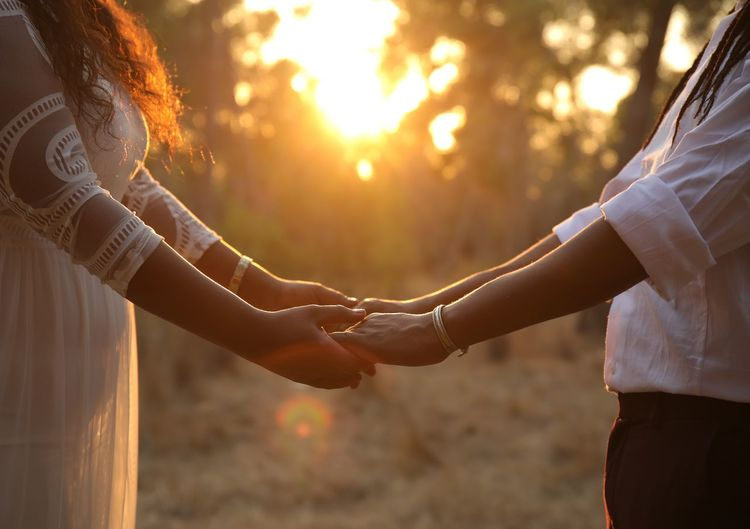 Midsection of couple holding hands while standing at park during sunset