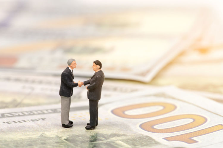 Businessmen figurines shaking hands on paper currency