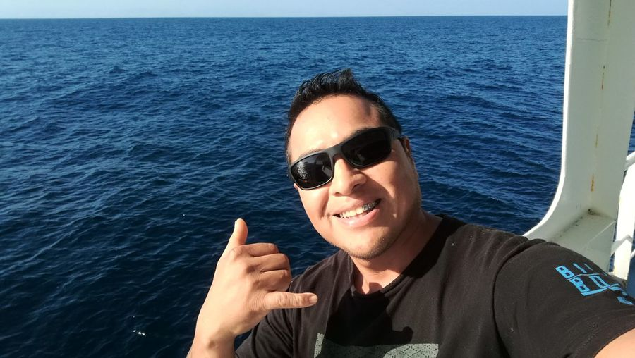 Man gesturing shaka sign in boat at sea