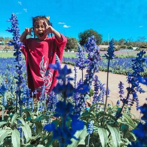 Portrait of smiling girl standing amidst flowering plant against sky