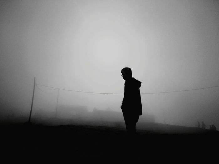 Silhouette Man Standing On Field Against Sky During Foggy Weather